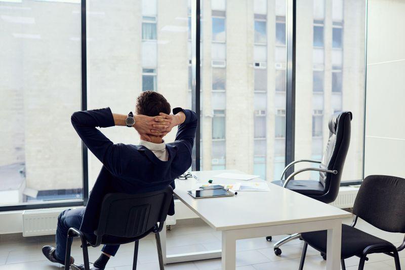 Mužv kancelárii s rukami za hlavou